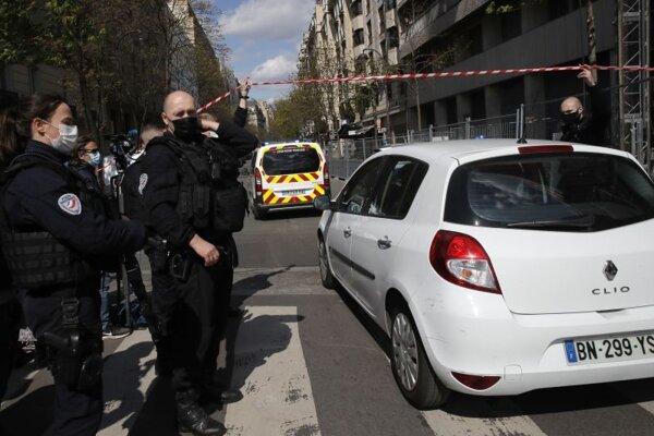 Policajti púšťajú cez policajnú pásku sanitku a policajné auto, ktoré prichádzajú na miesto činu po streľbe v Paríži 12. apríla 2021. Jedna osoba prišla v pondelok o život a ďalšia utrpela zranenia počas streľby pred budovou jednej z nemocníc v Paríži.