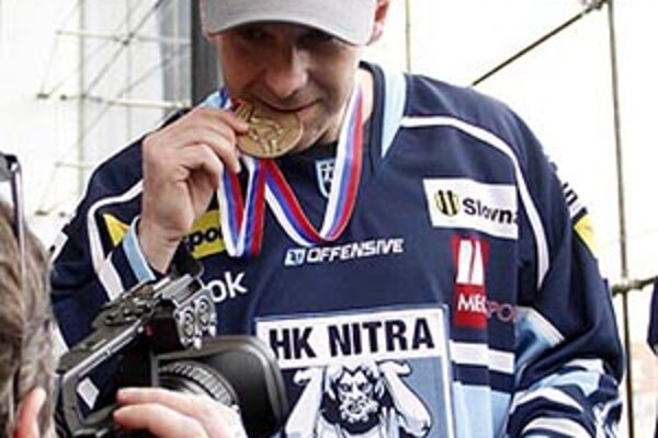 Český obranca Lubomír Vosátko pózuje s medailou v zuboch.