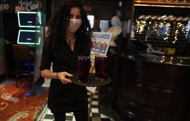 Čašníčka odnáša prvý čapovaný cider v pube Shakespeare's Head v Londýne.