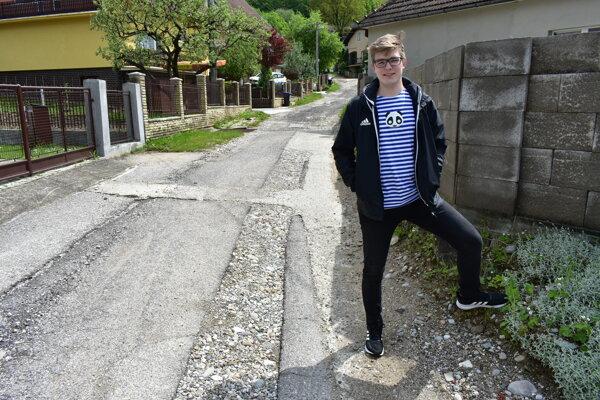 Pri silných dažďoch vznikajú na ceste jamy avyplavujú sa sedimenty. Na fotke poslanec Martin Trepáč na ulici Volavé.