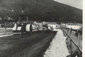 Pokladanie asfaltu na moste, ktorý vedie do obce v 50-tych rokoch 20. storočia.