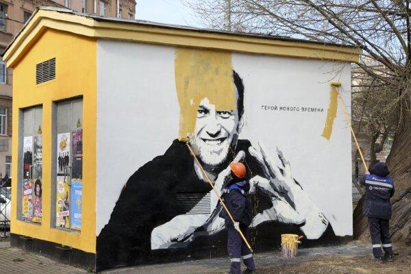 Pracovníci pretierajú farbou graffiti ruského opozičného lídra Alexeja Navaľného s nápisom Hrdina našej doby 28. apríla 2021 v Petrohrade.