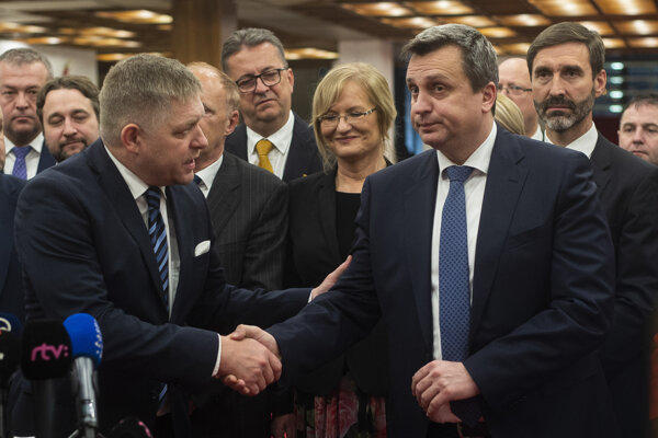 Predseda Smeru Robert Fico si podáva ruku s predsedom SNS Andrejom Dankom po schválení 13. dôchodku v parlamente vo februári 2020.