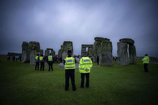 Hliadkujúci policajti megalitickom monumente Stonehenge.