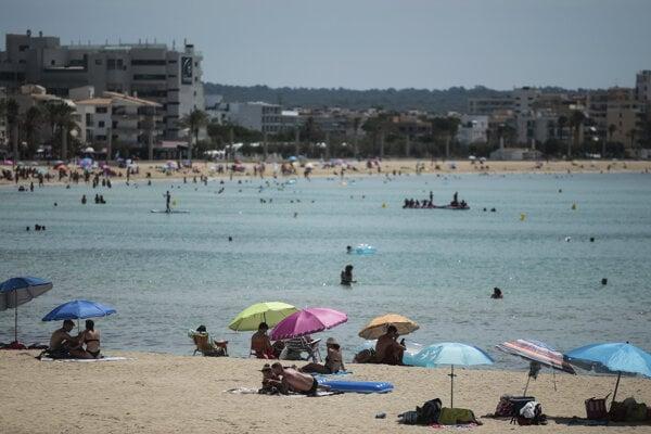 Ľudia sa opaľujú na pláži v Palme de Mallorca, hlavnom meste španielskeho ostrova Malorka.