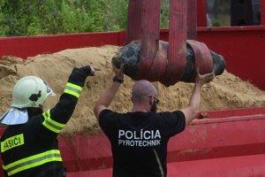 Policajný pyrotechnik a hasič dohliadajú na vykladanie bomby.