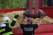 Policajný pyrotechnik a hasič vykladajú bombu na mieste zneškodnenia.