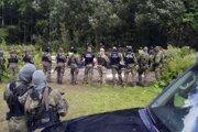 Poľská pohraničná polícia stráži skupinu migrantov na poľsko-bieloruskom pohraničí.