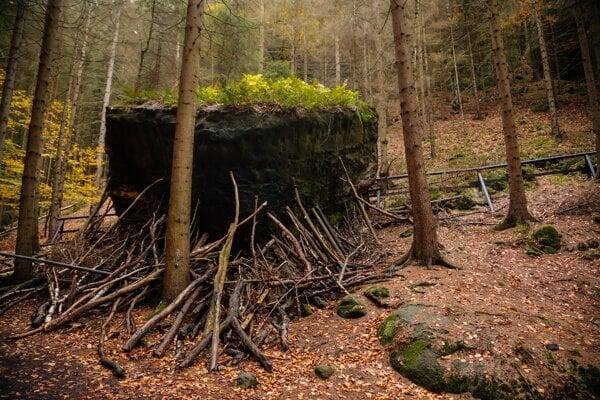 Turisti pokladajú konáre pod skaly. Zdá sa, ako by ich chceli podprieť. Ilustračný záber je z Českého Švajčiarska.