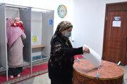 Žena hádže do urny lístok v prezidentských voľbách v uzbeckom Taškente.