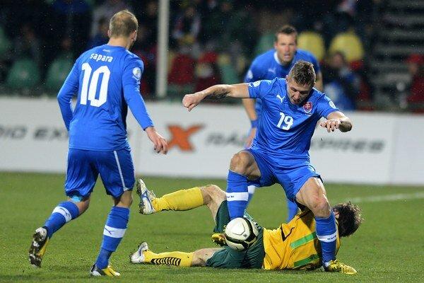Slovenskí futbalisti sa stretli s Litvou už v kvalifikácii o postup na MS 2014. Na snímke Juraj Kucka (s číslom 19) sa pokúša prejsť s loptou cez ležiaceho Mindaugasa Kalonasa.