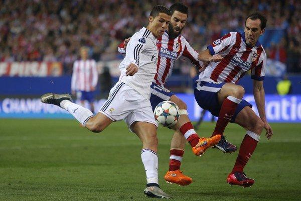 Cristiano Ronaldo (v bielom) sa dostáva do zakončenia. Zblokovať jeho pokus sa snaží dvojica hráčov Atlética - Diego Godín (vpravo) a Arda Turan.