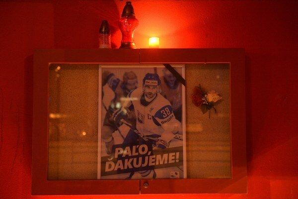 Sviečky horia pri portréte hokejistu Pavla Demitru pred vchodom na zimný štadión 7. septembra 2013 v Trenčíne. Vtedy to boli dva roky od tragédie.