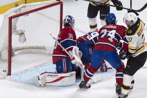 Patrice Bergeron z Bostonu prekonáva Petra Budaja z Montrealu.