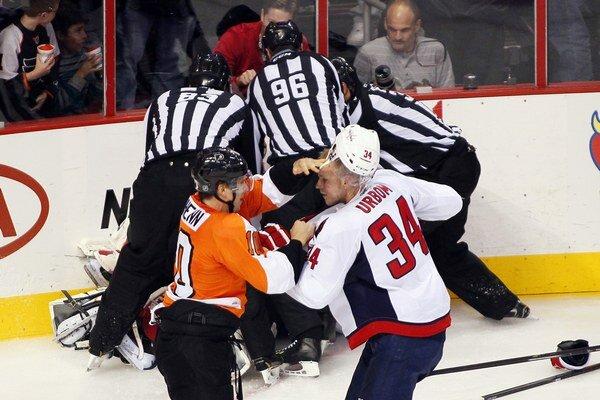 Brayden Schenn z Philadelphie (vľavo) a Alexander Urbom. Za nimi sa rozhodcovia snažia rozpliesť duo bitkárov Ray Emery a Brayden Holtby.
