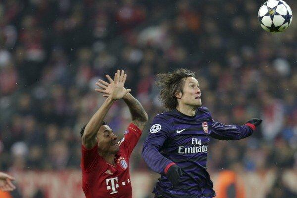 Hráč Arsenalu Londýn Tomáš Rosický (vpravo) bojuje o loptu s Luizom Gustavom z Bayernu Mníchov.