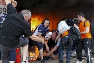Zraneného člena tímu Williams vynášajú z priestorov, kde vypukol požiar.