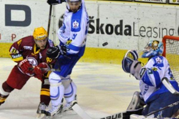 Hráč Dukly Trenčín Peter Kopecký (vľavo) v šanci pred brankárom HK Poprad Marcelom Melicherčíkom (vpravo), všetko sleduje Peter Klouda z HK Poprad (uprostred)