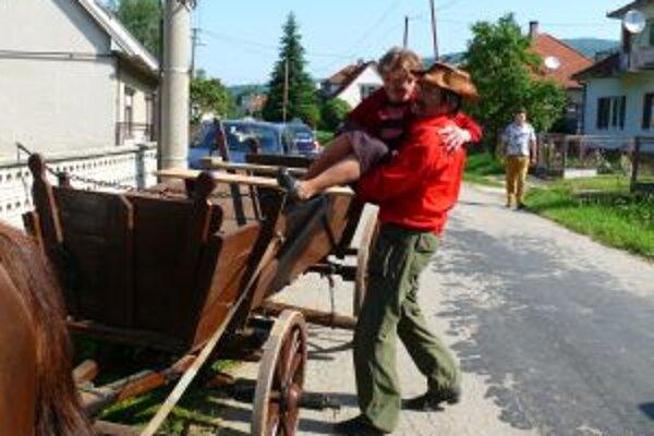 Kočiš Štefan Drobný pomáha na voz naložiť pasažierku Katarínu Bačovú. Takto na voze sa vybrali do volebnej miestnosti v časti obce Moravské Lieskové, Bučkovec.