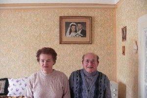 Manželia Sahajovci po šesťdesiatich rokoch manželstva (v pozadí na stene ich svadobná fotografia)