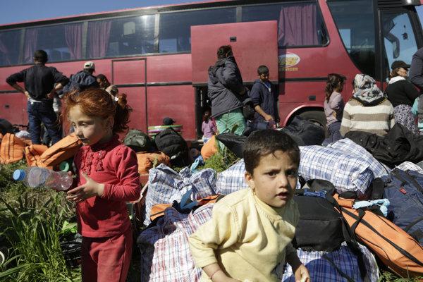 Jezídske deti sa hrajú pred autobusom, ktorý ich má odviezť z tábora v Idomeni.