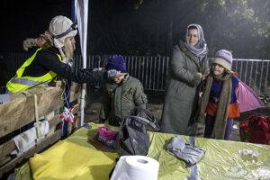 Dobrovoľníci rozdávajú prechádzajúcim utečencom čisté šaty.