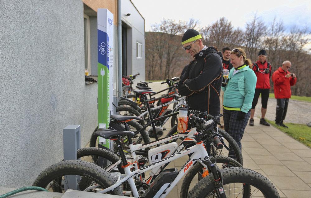 Prví cyklisti si nabíjajú elektrobicykle počas otvorenia prvej verejnej nabíjacej stanice.