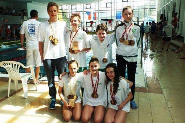 Výprava mladých novozámockých plavcov takto pózovala so získanými medailami.