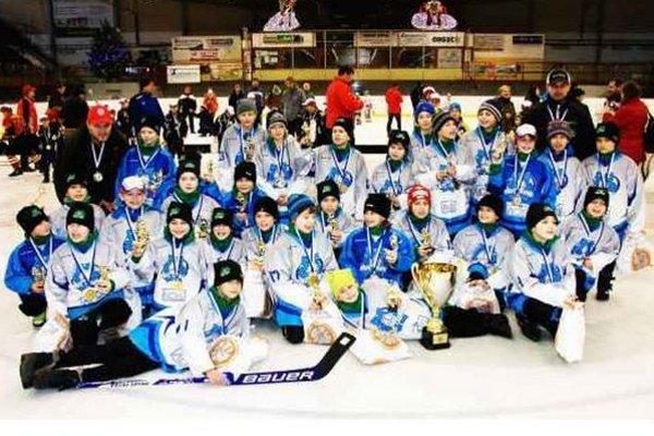 Mladí hokejisti 4 ŠHT Lokomotíva Nové Zámky s pohárom pre víťazov po slávnostnom vyhlásení výsledkov.