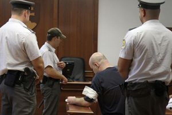 Štefan K. (uprostred), obvinený z úkladnej vraždy bývalého primátora a hlavného kontrolóra Hurbanova Lászlóa Basternáka, v pojednávacej miestnosti pred verejným zasadnutím v Pezinku 6. júna