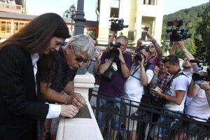 Francúzska herečka Chiara Mastroianni (vľavo) a sochár Igor Mosný (druhý zľava) pripevňujú tabuľku Umelcova misia na festivalový Most slávy 25. júna 2016 na Medzinárodnom filmovom festivale v Trenčianskych Tepliciach.