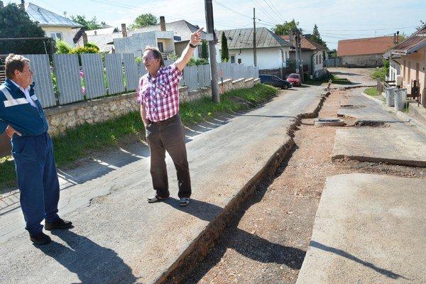 Do dvorov sa autá nedostanú. Podľa Eduarda Jasaňa (so zdvihnutou rukou) sa na oprave ciest nerobilo trištvrte roka vôbec nič.