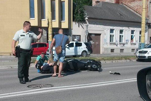 Po nehode. Motocyklista zostal ležať zranený na zemi.