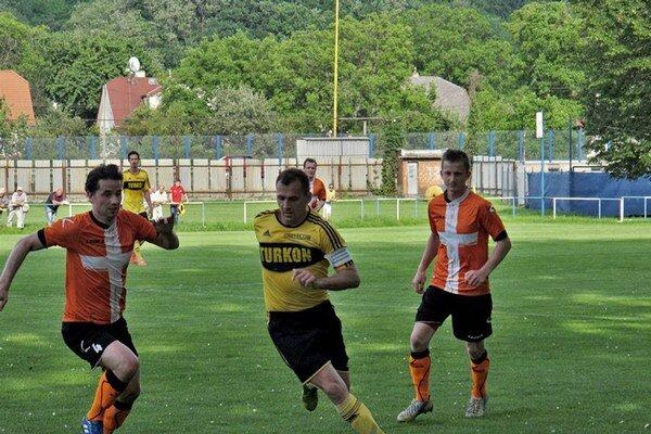Kapitán. Medzi dvojicou hráčov Plavnice Kovalíkom (vľavo) a Genčúrom sa ocitol strelec tretieho gólu Opátskeho Turzcyk.