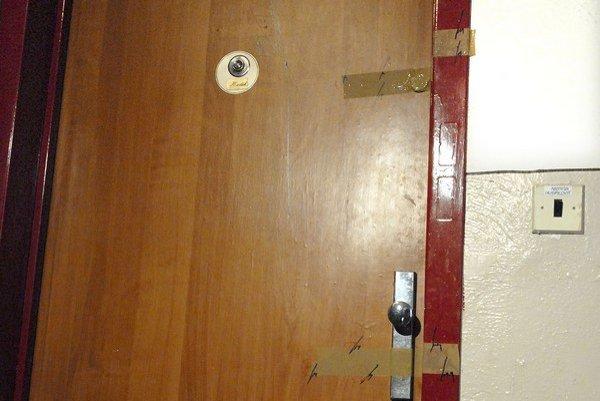 Zapečatené dvere. Sú na nich stopy po úderoch a kopancoch.