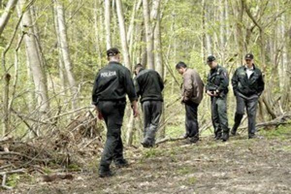 Miesto činu. Policajti prezerajú priestor, kde leží telo.