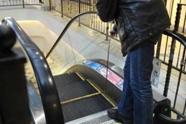 Eskalátor. Zábradlie má od schodíka po držadlá výšku 100 centimetrov.