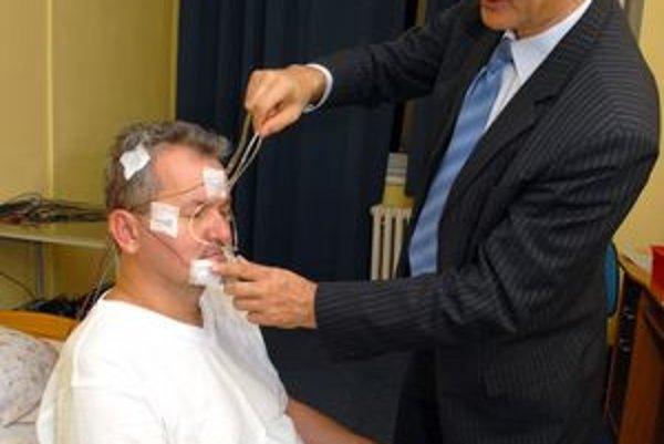 V. Donič pripína elektródy na hlavu pacienta.