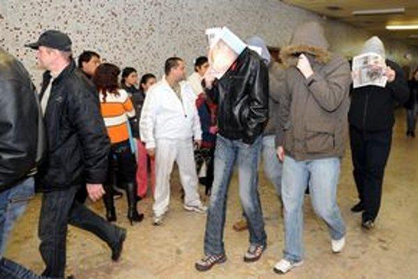 Obvinení bývalí policajti si zakrývajú tváre, v pozadí rodičia a príbuzní šikanovaných detí.
