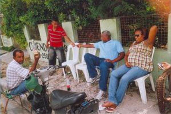 Celestinini priatelia sedia pred jej domom v La Romane.