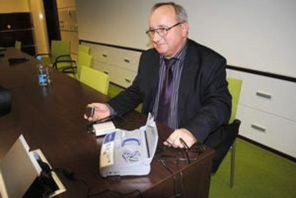 Košičan Jozef. V ruke so zariadením sledujúcim jeho srdce a modemom v popredí, ktorý informácie prenáša do počítača lekára.