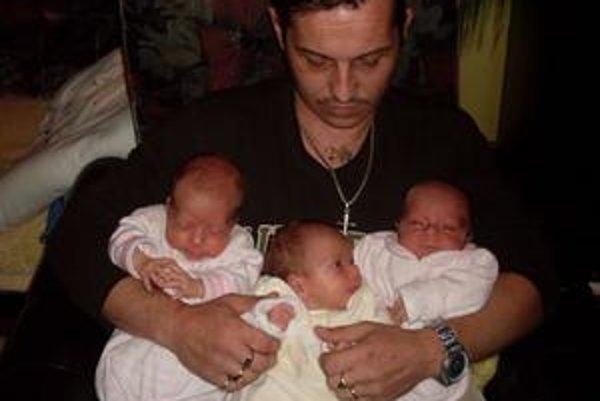 Šťastný otecko s troma dievčenskými batôžkami v náručí.