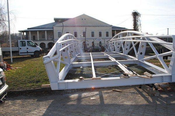 Nová lávka. Robotníci na brehoch potoka ukotvili mostík z kovu a dreva.