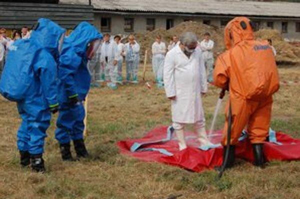 Dekontaminácia. Pomáhajú s ňou hasiči oblečení v pretlakových oblekoch.