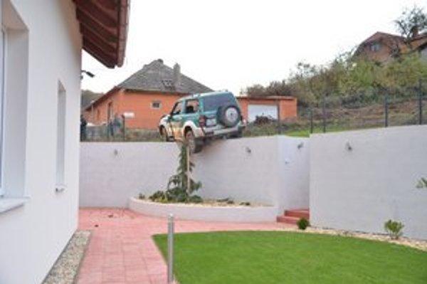 Nehoda. Auto dostalo na nespevnenom povrchu šmyk a skončilo na plote domu.