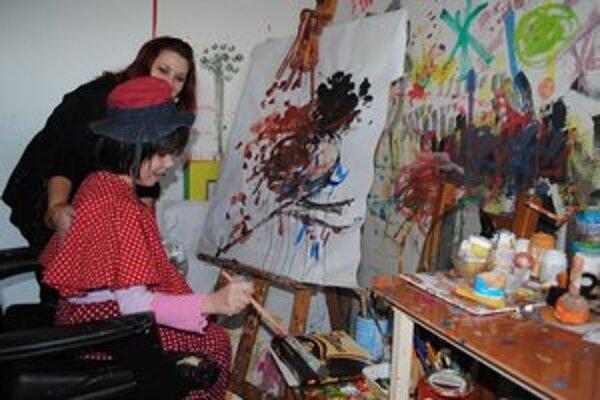 Malá maliarka s učiteľkou pri arteterapii.