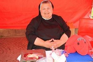 Sestra Maristella. Predáva v stánku, z ktorého výťažok poputuje núdznym.