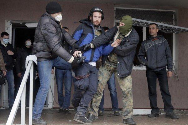 Maskovaní proruskí radikáli napádajú britského novinára Fredericka Paxtona vo východoukrajinskom meste Horlivka.