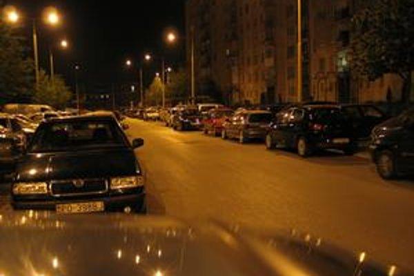 Nočné parkovanie. Väčšina áut je zablokovaná. Autá sú zaparkované tesne vedľa seba.