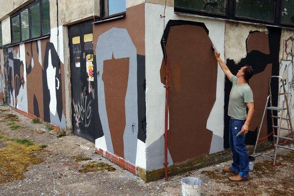 Maliar Milan Ladyka pracuje na umeleckom zásahu na kotolni sídliska Sever v Trebišove s názvom Portréty (pre) obyvateľov sídliska.